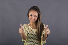 Smiling casual young woman posing thumbs up Stock Photography