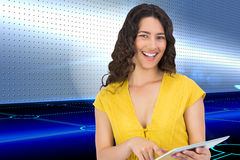 Smiling casual young woman scrolling on her tablet computer Stock Image