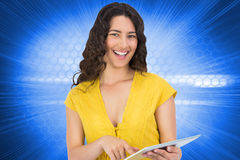 Smiling casual young woman scrolling on her tablet computer Stock Photo