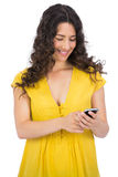 Smiling casual young woman texting on her phone Royalty Free Stock Photo
