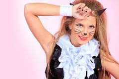 Smiling cat. Portrait of a sexy playgirl in pussycat costume alluring over pink background Royalty Free Stock Photo