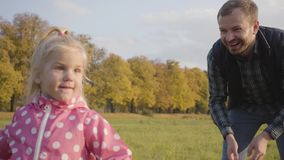Smiling caucasian bearded man teaching his little daughter to play soap bubbles. Cute blonde girl dressed in dotted pink. Jacket spending autumn day with her stock video footage