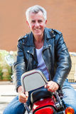 Smiling Caucasian biker sat back. Color vertical portrait of a trendy fashion driven senior motor cyclist sat back to front on red cruiser smiling holding onto Stock Images