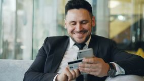 Smiling Caucasian businessman in suit using online banking holding credit card and smartphone in his hands in modern. Cheerful Caucasian businessman in suit stock video footage