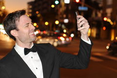 Smiling Caucasian businessman taking a selfie on street at night Royalty Free Stock Photo