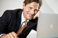 Smiling Caucasian businessman using laptop Royalty Free Stock Images