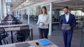 Two colleagues talking at work. Smiling caucasian businesswoman holding folder with documents walking around the office. handsome adult businessman heading to stock video