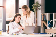 Smiling caucasian businesswomen in formalwear talking while working at modern office. Young smiling caucasian businesswomen in formalwear talking while working Stock Photography