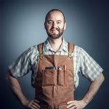 Smiling wood worker. Smiling caucasian carpenter with apron, studio shot portrait stock photography