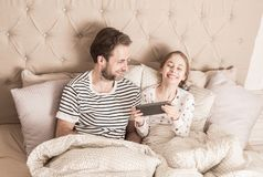 Family having fun while using tablet in a bed Stock Photos