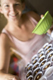 Smiling caucasian girl baking chocolate cupcakes Stock Photography