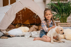 Smiling caucasian girl hugging labrador puppy at home Royalty Free Stock Images