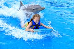 Happy Caucasian girl swimming with dolphin. Smiling Caucasian girl on wake board with dolphin in swimming pool stock photos
