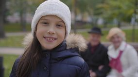Smiling Caucasian girl in white hat turning to her grandparents sitting on the bench in the background and waving. Cheerful child spending autumn day with stock footage