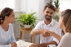 Smiling caucasian male manager, partner shaking hands thanking coworker royalty free stock photo