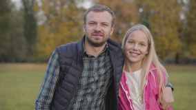 Smiling caucasian man approaching to the young blonde girl on the foreground and hugging her. Father making piece with. His teen daughter dressed in pink jacket stock video