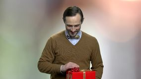 Smiling caucasian man giving gift box. Handsome bearded man handing wrapped gift box on blurred background. Gift for Valentines Day stock video footage