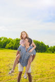 Smiling Caucasian Man Giving Woman Piggyback Ride Outdoors. Yout Stock Images