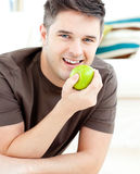 Smiling caucasian man holding an apple smiling Royalty Free Stock Photography