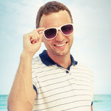 Smiling Caucasian man standing with white sunglasses Royalty Free Stock Image