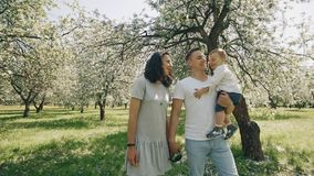 Smiling caucasian parents walking with son in summer apple tree park. Smiling caucasian parents walking with son son in summer apple tree park. Happy family stock video footage