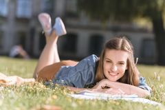 Young woman studying in park. Smiling caucasian student looking at camera while doing homework in park Stock Images