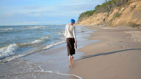Smiling caucasian woman in blue turban walking on the beach enjoying life. Holidays concept stock video footage