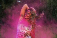 Smiling caucasian woman in a cloud of pink dry paint, celebrating Holi festival. Smiling caucasian girl in a cloud of pink dry paint, celebrating Holi festival stock photo