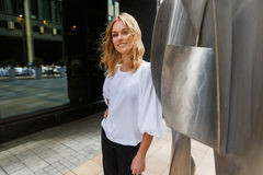 Smiling caucasian woman with curly blonde hair nearby steel sculpture Stock Photos