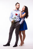 Smiling caucasian woman hugging her boyfriend  holding the rose Royalty Free Stock Photos