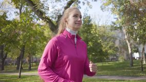 Smiling Caucasian woman in pink sportswear and headphones running in the autumn park. Female runner training in the. Morning outdoors. Sports concept stock footage