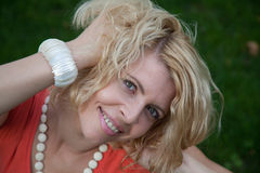 Smiling caucasian woman playing with her hair on the green fundal Royalty Free Stock Photos