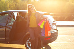 Smiling Caucasian woman putting her shopping bags into the car Stock Photo