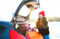 Smiling Caucasian woman putting her shopping bags into the car t Stock Photo