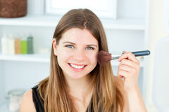 Smiling caucasian woman putting powder on her face Royalty Free Stock Photography