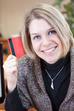 Smiling Caucasian woman showing credit card Royalty Free Stock Photography