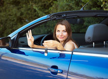 Smiling caucasian woman showing key in a cabriolet Stock Photography