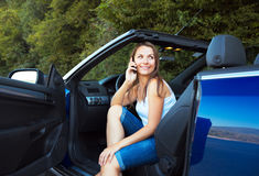 Smiling caucasian woman talking on phone in a cabriolet Royalty Free Stock Images