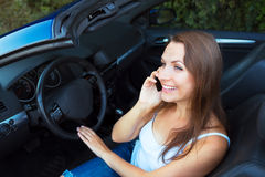 Smiling caucasian woman talking on phone in a cabriolet Royalty Free Stock Photo