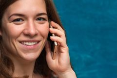 Smiling caucasian woman using her smartphone. Happy cheerful female looking at the camera and talking on the mobile phone. Portrait of beautiful smiling Royalty Free Stock Image