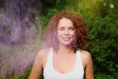 Smiling caucasian model with wavy hair playing with colorful dry. Smiling caucasian woman with wavy hair playing with colorful dry paint at the Holi Festival stock images