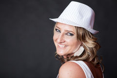 Smiling Caucasian woman wearing a pinstrip white hat Stock Image