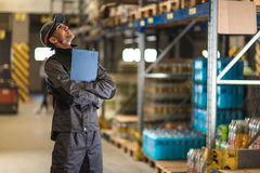 Smiling caucasian worker with clipboard looking up in warehouse. Industrial theme Stock Images
