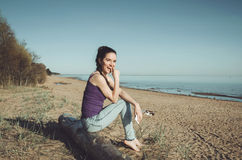 Smiling caucasian young woman in casual jeans clothes, sitting on a wooden log  the coast river. Brunette female walking. Smiling caucasian young woman in casual Royalty Free Stock Photos