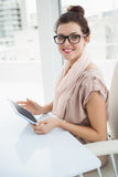 Smiling causal businesswoman using tablet Royalty Free Stock Image