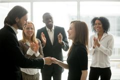 Smiling ceo handshaking successful female worker showing respect. Smiling ceo promoting rewarding handshaking motivating female worker congratulating with royalty free stock image