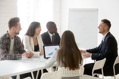 Smiling ceo leading meeting talking to multiracial team in offic. Smiling ceo talking to multiracial team at office meeting, friendly executive discussing good royalty free stock image
