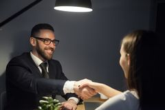 Happy male shaking hand of female job applicant during interview royalty free stock photo