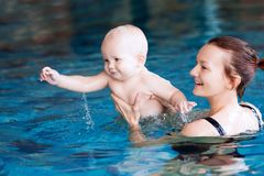 Smiling charming baby in swimming pool. Mother teaching baby to swim. Portrait of a charming 11 months child in the classroom in a swimming pool. Healthy Family Stock Photos