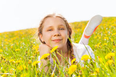 Smiling charming girl laying in dandelion  meadow Stock Images